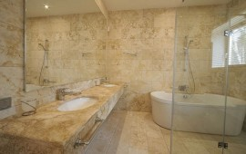 Облицовка стен помещения под ванную натуральным камнем.